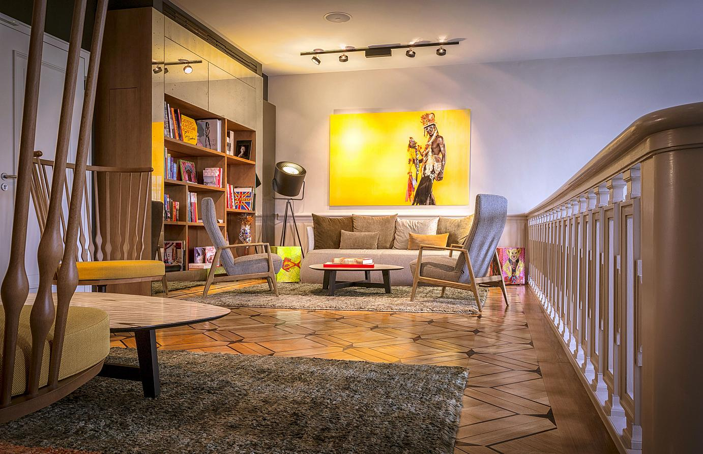 Comfy and relaxed: the Library in the historical front part of the building. Each storey profits from an expansive landing spreading between staircase and guestroom corridors. Bearing witness to the structure's grand  history are authentic parquet  floors, French doors or original decorative elements restored back to their former beauty. The three-storey library holds a wealth of books on art, architecture and culture and – as a tribute to the nearby zoo - randomly positioned animal figures. Embellishing handicraft, photographs and Cajons from Panama dowse to the third floor into a colourful and cozy atmosphere.